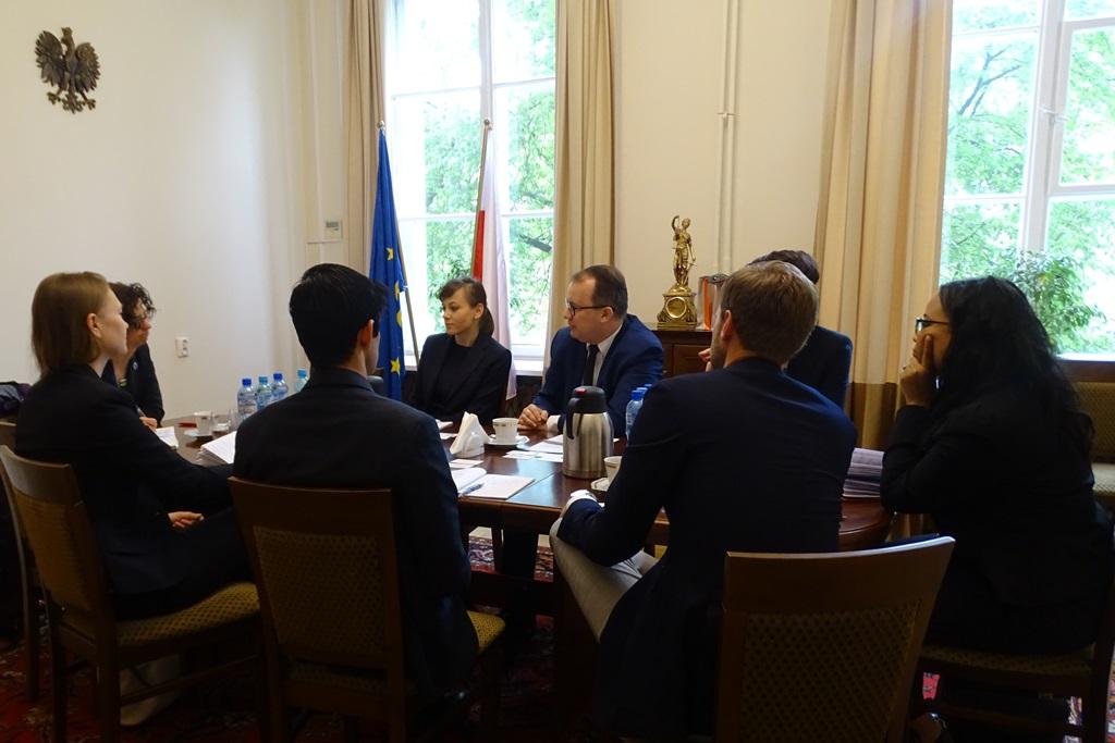 zdjęcie: kilka osoób siedzi wokół brązowego stołu