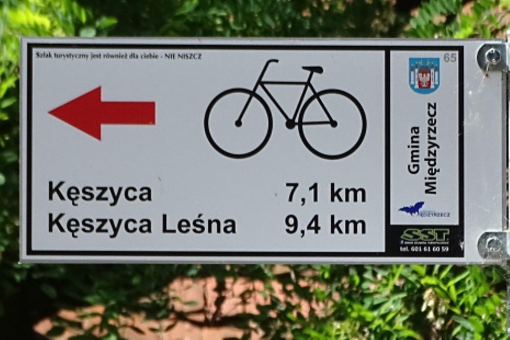 Zdjęcie: rower i strzałka na tabliczce informacyjnej o trasie rowerowej