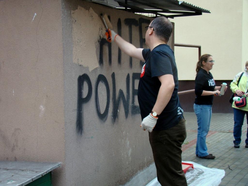 Zdjęcie: mężczyzna w czarnej koszulce zamalowuje napis ma ścianei