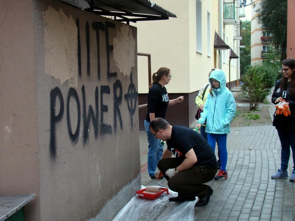 Zdjęcie: ludzie w koszulkach i z napisem HejtStop i w sportowych strojach przy ścianie z hejterskimi napisami