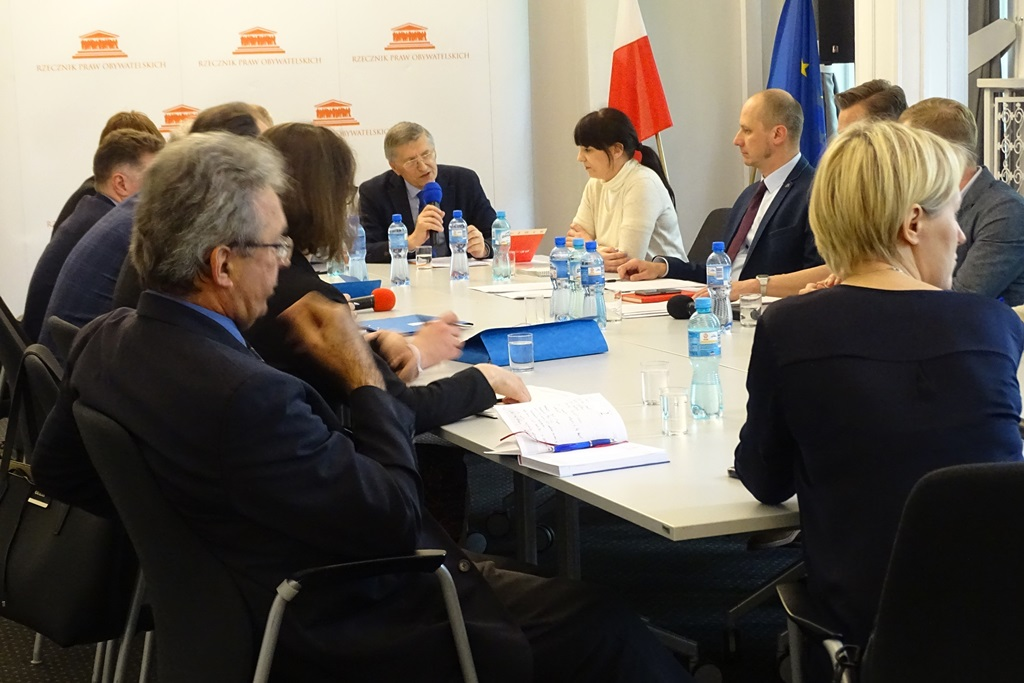 zdjęcie: przy stołach siedzi kilkanaście osób, mężczyzna w okularach mówi do mikrofonu