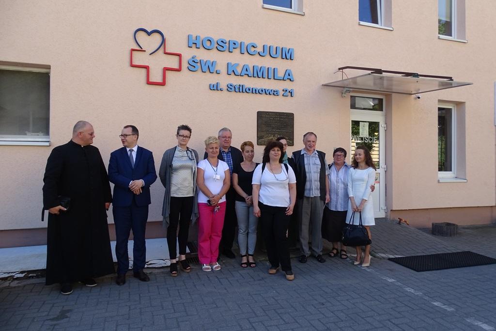 Zdjęcie: grupa ludzi przed budynkiem z napisem Hospicjum. Jest wśród nich ksiądz