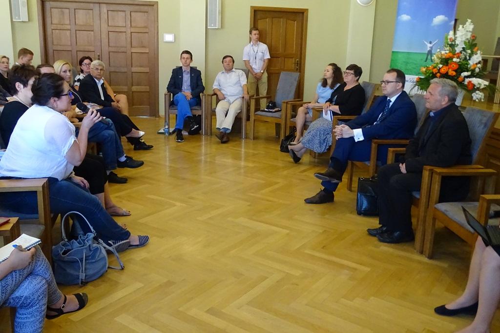 Zdjęcie: ludzie siedzą w kręgu, mówi kobieta