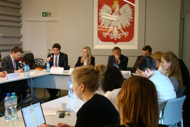 zdjęcie: przy złączonych stołach siedzi kilkanaście osób