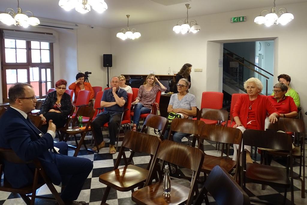 Zdjęcie: grupa ludzi rozmawia w zabytkowym wnętrzu. Czerwone elementy wyposażenia i czerwone elementy ubrań