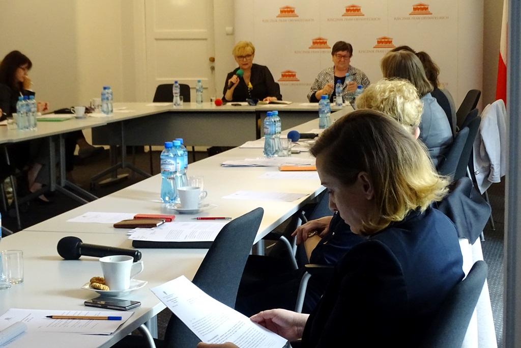 zdjęcie: kilka osób siedzi prz białych stołach, kobieta po prawej stronie czyta dokumenty