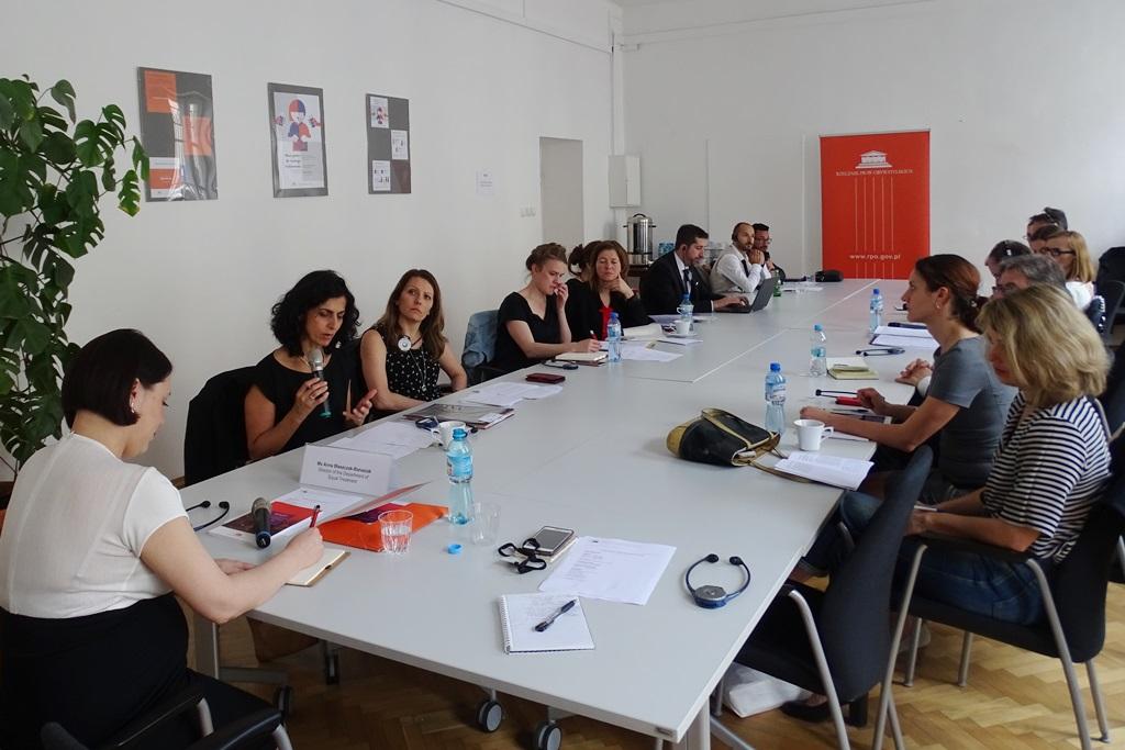 zdjęcie: przy białym stole siedzi kilkanaście osób