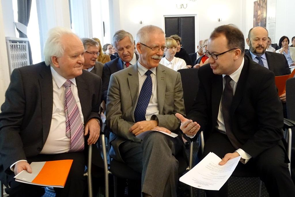 zdjęcie: trzej mężczyźni siedzą i rozmawiają