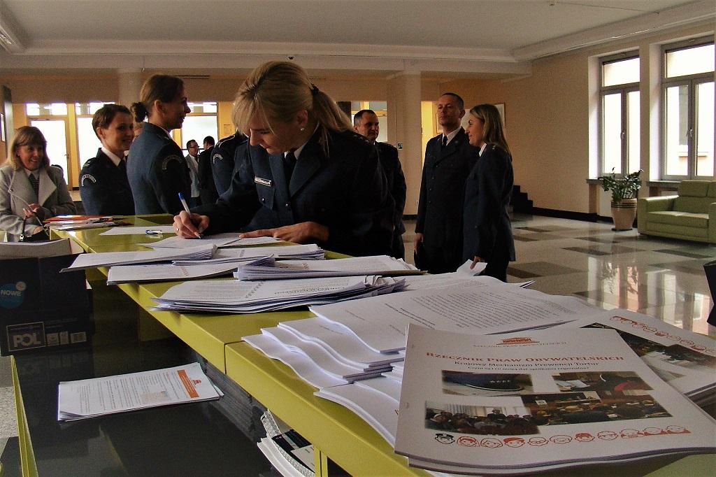 zdjęcie: na blacie leżą materiały informacyjne, kilka osób w mundurach stoi i je przegląda
