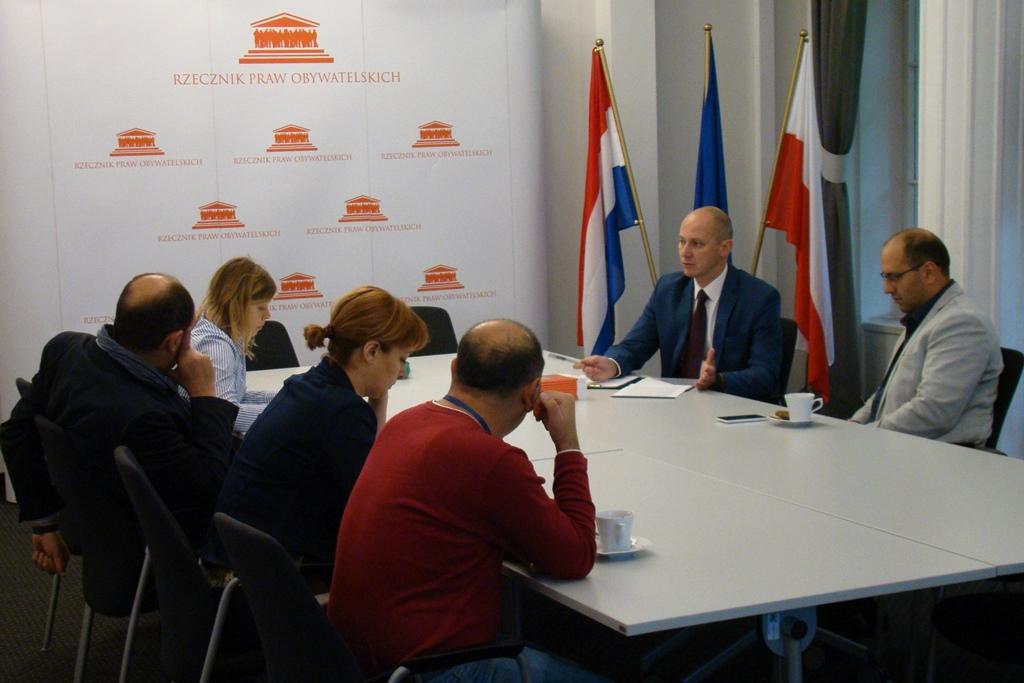 zdjęcie: prz białym stole siedzi kilka osób, w tle widać flagi