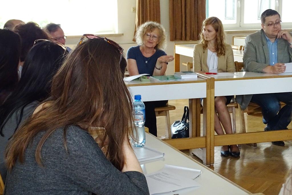 zdjęcie: kilka osób siedzi przy stołach ustawionych w kwadrat, na wprost siedzą dwie kobiety i mężczyzna, po lewej widać kilka osób siedzących bokiem