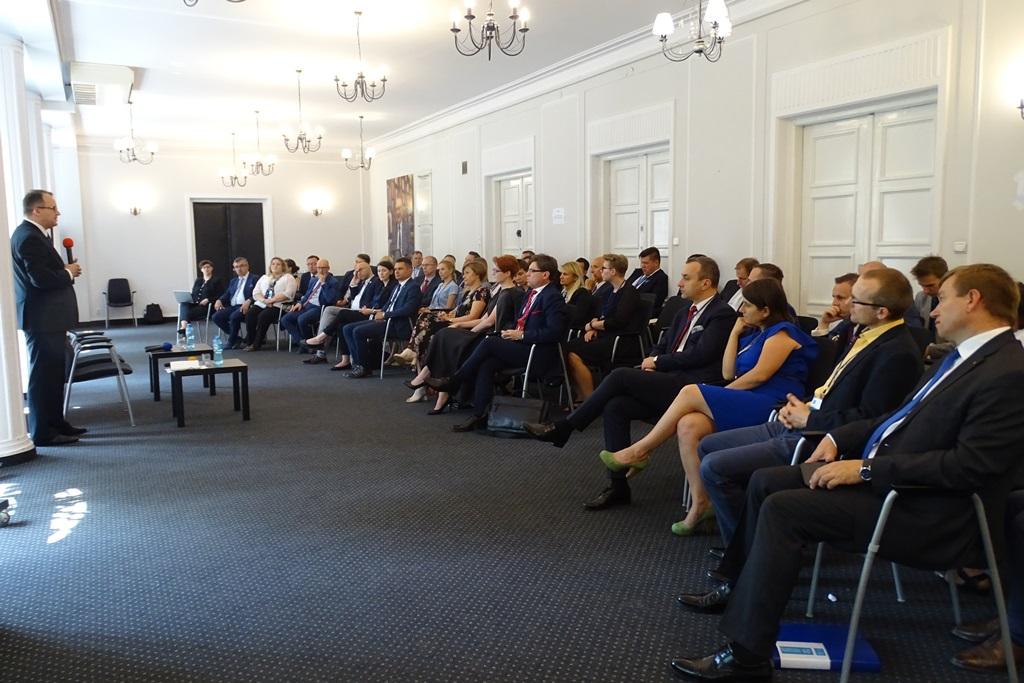 zdjęcie: na sali siedzi kilkadziesiąt osób przed nimi stoi mężczyzna