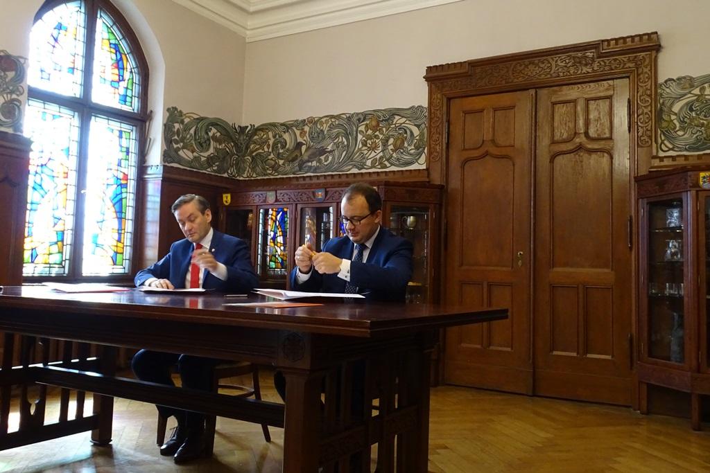Zdjęcie: dwaj mężczyźni podpisują dokumenty przy stole
