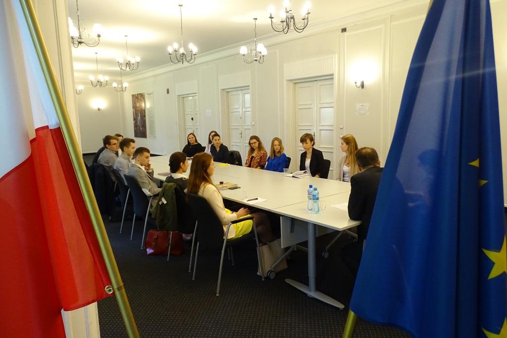 zdjęcie: na pierwszym planie flaga Polski i Unii Europejskiej za nimi, przy stole siedzi kilkanaście osób