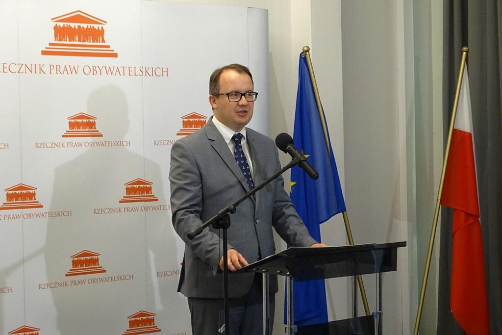 zdjęcie: mężczyzna w jasnym garniturze stoi przy mónicy, za nim widać polską i europejską flagę