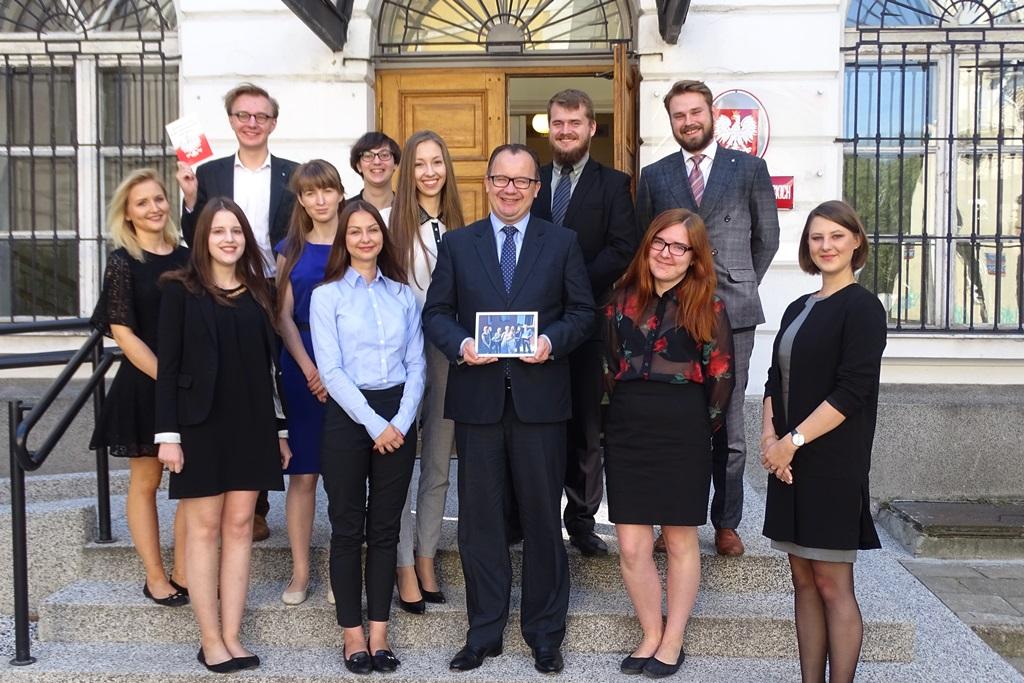 zdjęcie: kilkanaście osób stoi na schodach przed budynkiem i pozuje do zdjęcia