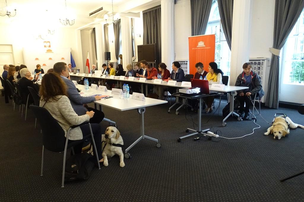 zdjęcie: przy stołach ustawionych w literę U siedzi kilkanaście osób, przy brzegach stołów siedzą dwa psy przewodniki