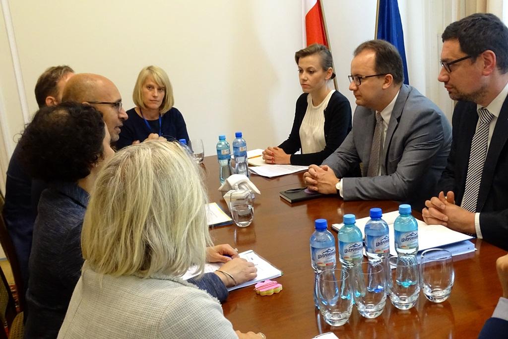 zdjęcie: przy brązowym stole siedzi kilka osób