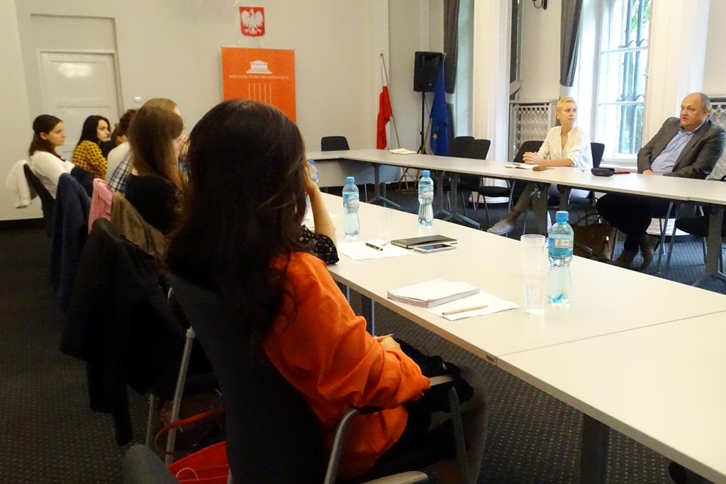 zdjęcie: po lewej stronie 9 osób siedzi przy stole, po drugiej stronie siedzi mężczyzna i kobieta