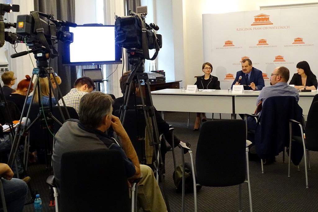 zdjęcie: w tle widać stół za którym siedzą dwie kobiet i mężczyzna, przed nimi na krzesłach siedzi kilka osób, po środku widać ustawione kamery