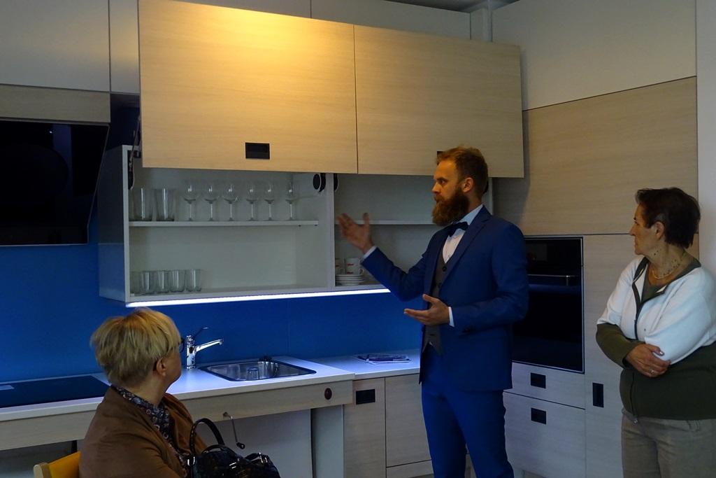 zdjęcie: mężczyzna w garniturze otwiera obniżone szafki