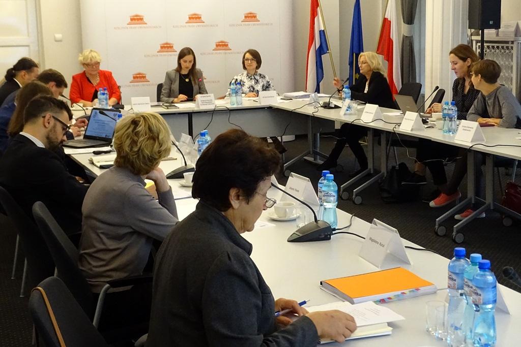 zdjęcie: przy białych stołach siedzi kilka osób
