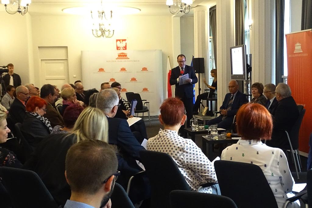 zdjęcie: kilkanaście osób siedzi na sali, przed nimi stoi mężczyzna w garniturze