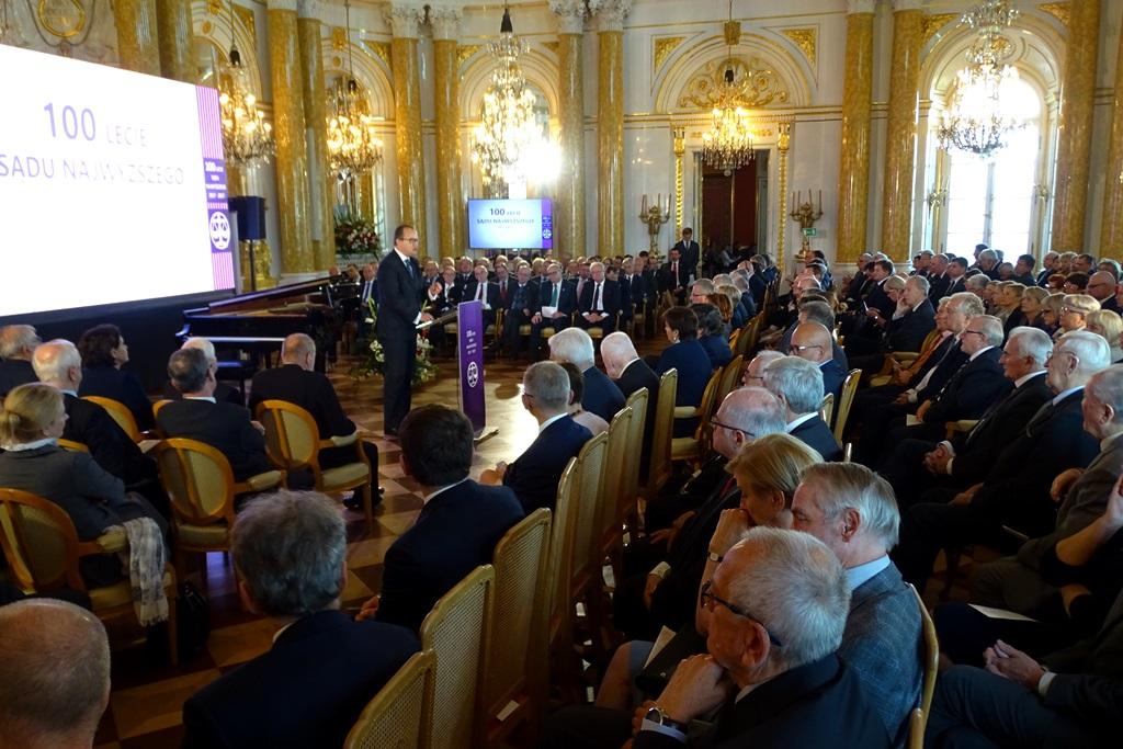 zdjęcie: kilkadzisiąt osób siedzi na tali tronowej mężczyzna w garniturze stoi na środku przy mównicy