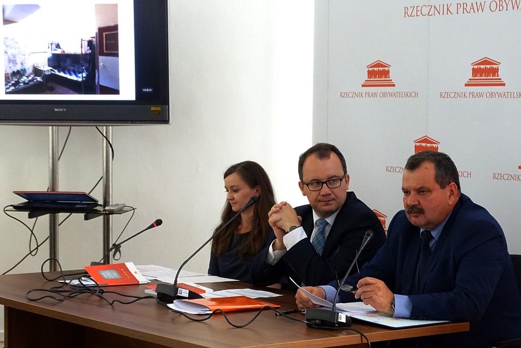 zdjęcie: trzy osoby siedzą przy stole, za nimi w tle widać ekran na ktowtym wyświetlane są zdjęcia z więzień