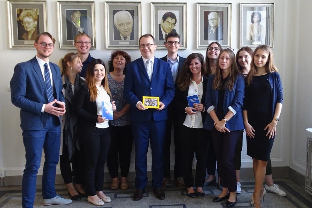 zdjęcie: grupa osób stoi, niektórzy z nich przymają w ręku niebieskie konstytucje, mężczyzna w garniturze po środku trzyma zdjęcie oprawione w żółtą ramkę