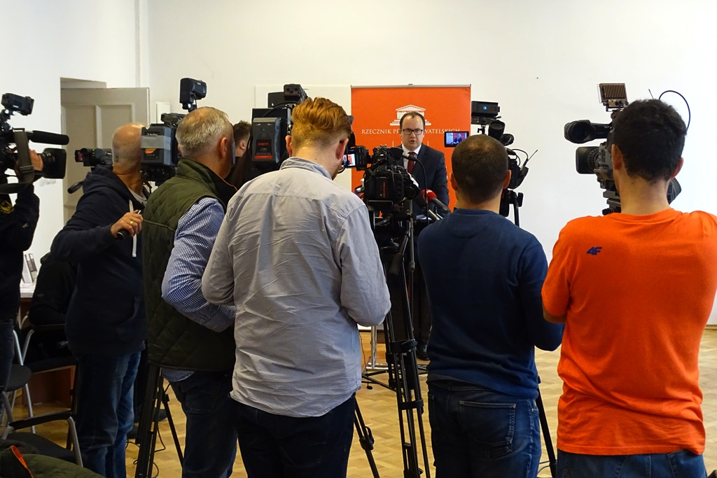 zdjęcie: kilka osób stoi przy kamerach przed nimi rzy mównicy stoi mężczyzna w garniturze