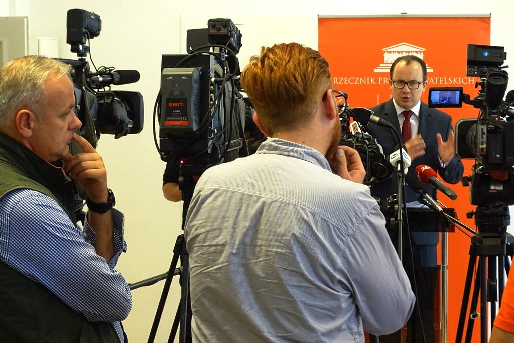 zdjęcie: na pierwszym planie dwóch mężczyzn przy kamerach przed nimi stoi mężczyzna w garniturze, który gestykuluje