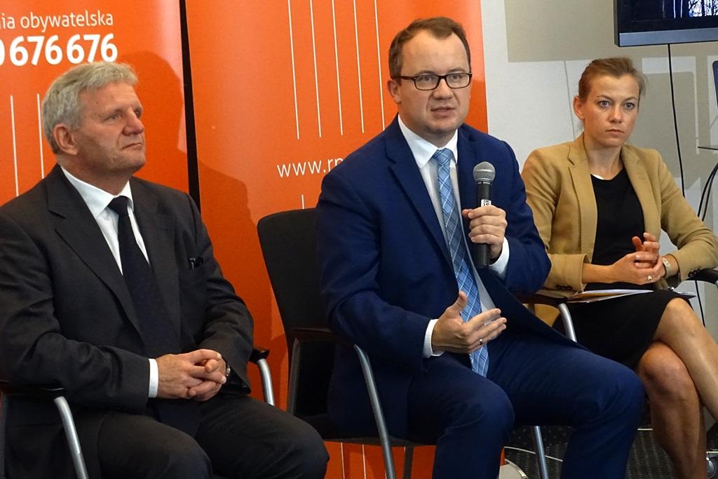 zdjęcie: od lewej siedzą dwaj mężczyźni w garniturach, drugi z nich trzyma mikron, obok niego siedzi kobieta