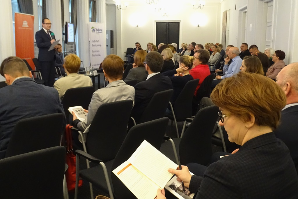 zdjęcie: kilkanaście osób siedzi na sali przed nimi stoi mężczyzna