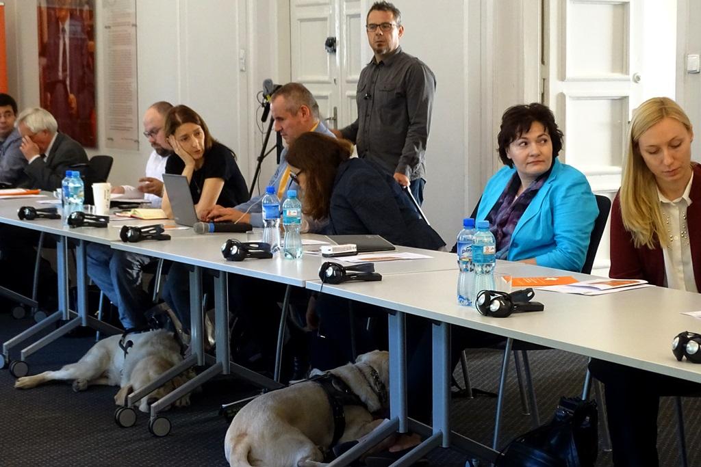 Zdjęcie: ludzie przy stole konferencyjnym, pod stołem - pies-przewodnik osoby niewidomej
