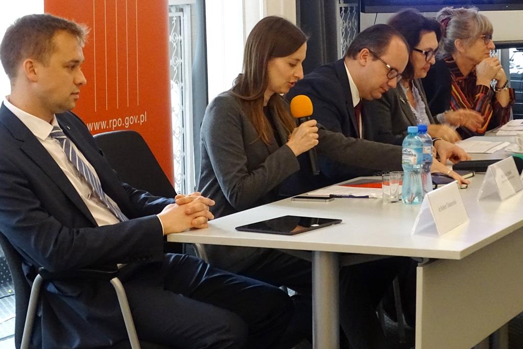 zdjęcie: trzy kobiety i dwaj mężczyźni siedzą przy tosle, jedna z kobiet mówi do mikrofonu