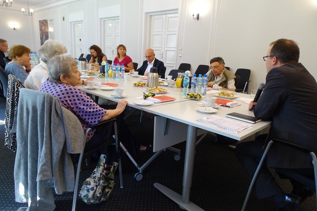 zdjęcie: kilka osób siedzi przy stole
