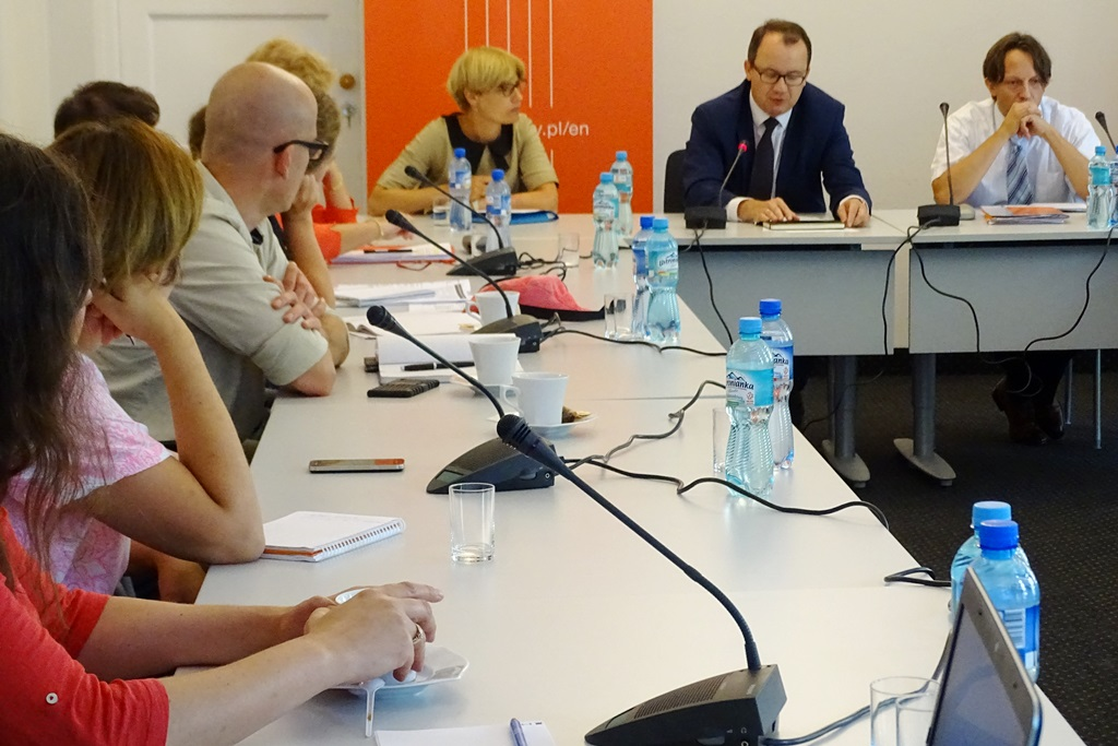 zdjęcie: po lewej stronie ludzie siedzą wdłuż stołu i patrzą na troje osób siedzących za stołem na wprost obiektywu