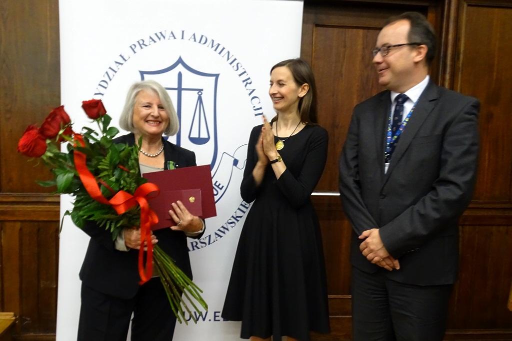zdjęcie: stoją dwie kobiety i mężczyzna pomiędzy nimi, kobieta po lewej trzyma czerwone róże