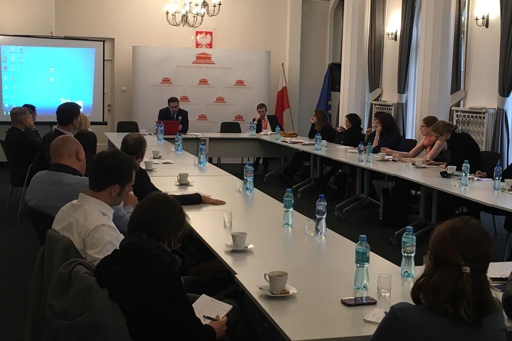 zdjęcie: kilkanaście osób siedzi przy stołach konferencyjnych
