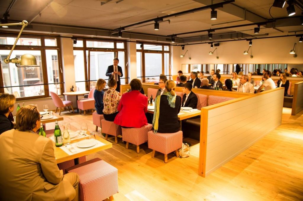 Ludzie słuchają stojącego mężczyzny siedząc przy stolikach