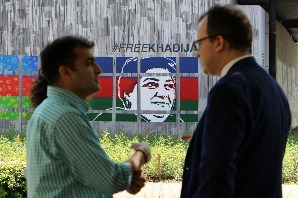 zdjęcie: dwaj mężczyźni rozmawiają, za nimi w tle widać fragment muralu przedstawiający twarz kobiety