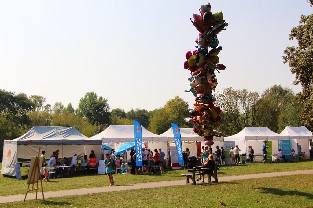 zdjęcie: na ławce siedzi dziewczyna trzymajaca kilkadziesiąt balonów za nią w tle widać namioty