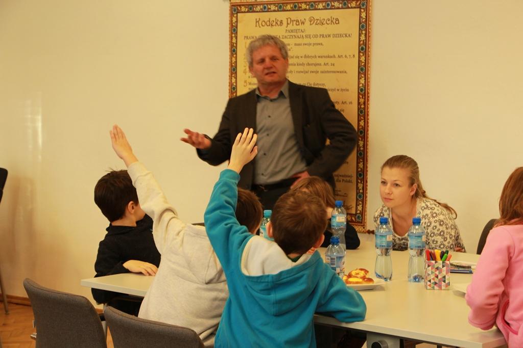 zdjęcie: mężczyzna stoi przy plakacie, obok niego przy stoliku siedzi kilkoro dzieci