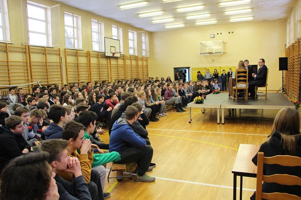 zdjęcie: po prawewj stronie na podwyższeniue siedzą trzy osoby, po lewej widać młodych ludzi siedzących na sali gimnastycznej