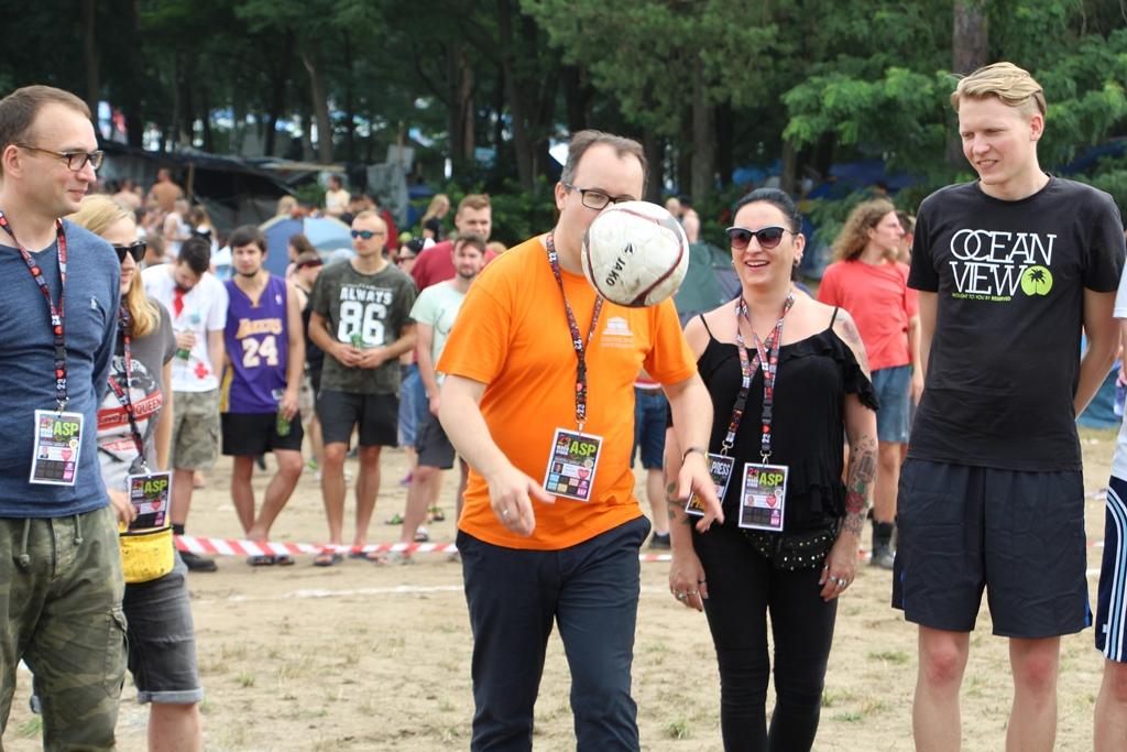 zdjęcie: mężczyzna w pomarańczowej koszulce kopie piłkę, kilka osób mu się przygląda