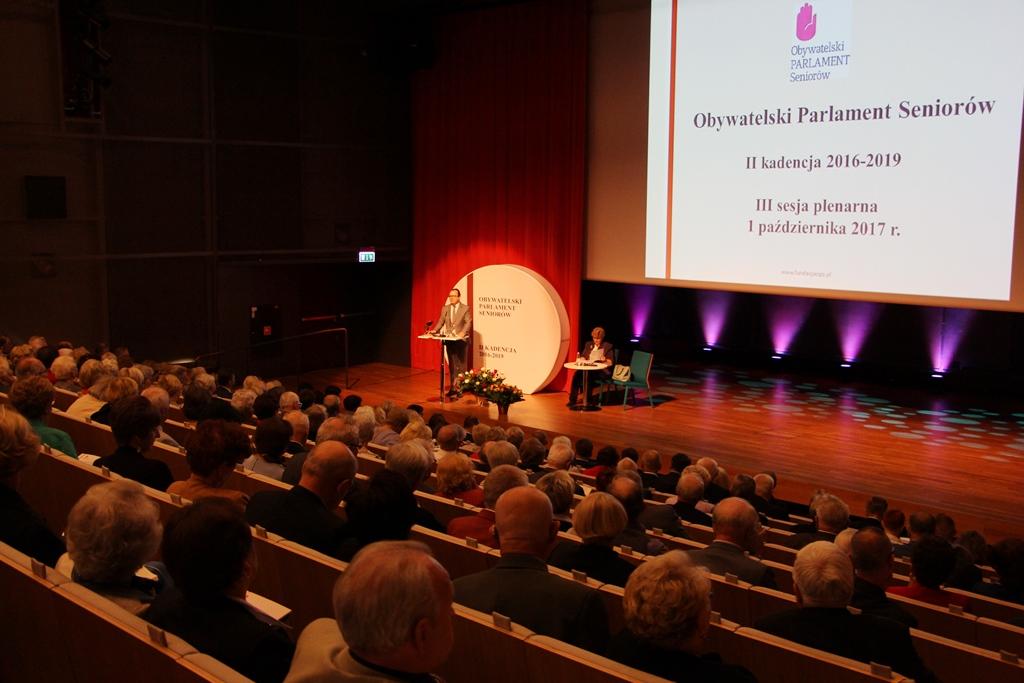 zdjęcie: mężczyzna stoi na scenie, przed nim kilkaset osób