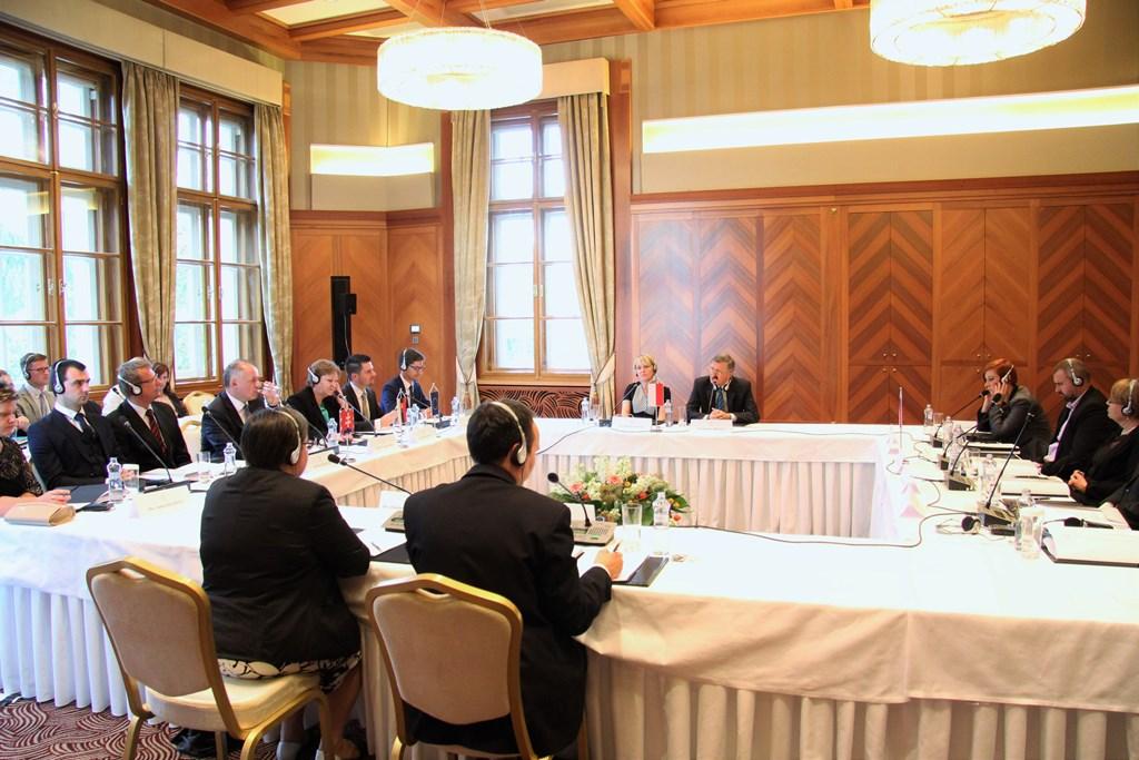 zdjęcie: kilkanaście osób siedzi przy stołach ustawionych w kwadrat