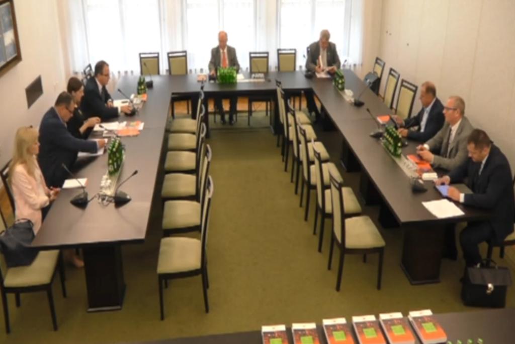 Zdjęcie: ludzie siedzą wokół stołu w kształcie litery U. Na pierwszym planie - książki