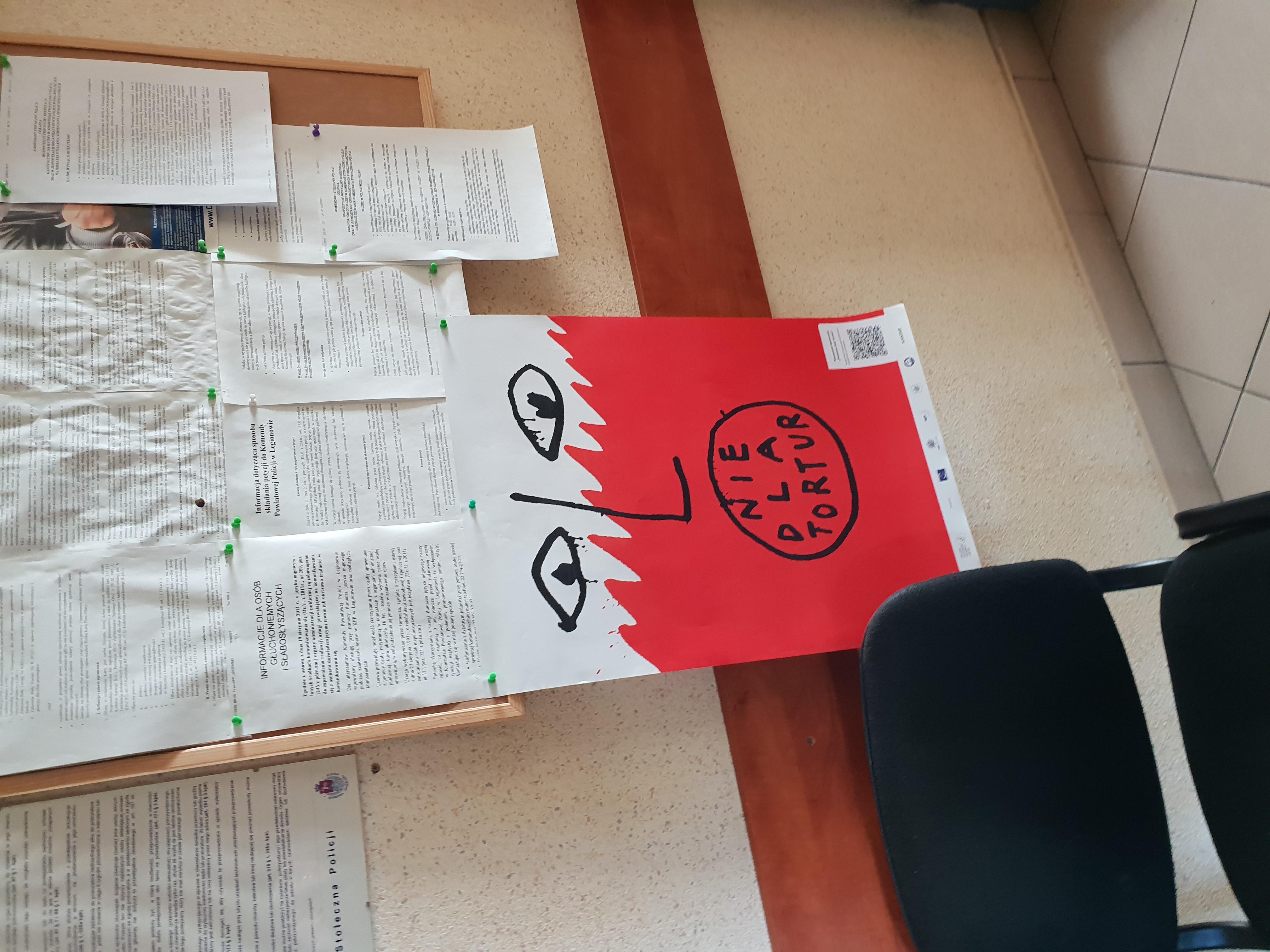 Na zdjęciu po lewej stronie widać krzesło, a nad nim znajduje się tablica korkowa, na której wisi plakat przedstawiający biało-czerwoną twarz z napisem: nie dla tortur